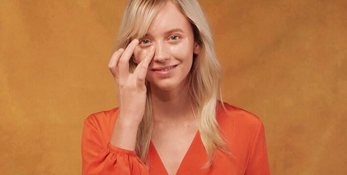 femme appliquant la crème pour les yeux sur un fond orange
